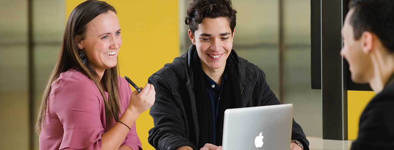 Two students sit in front of a computer.