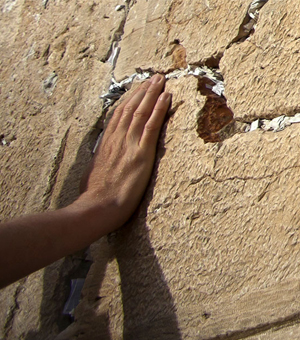 A hand caresses a cracked stone wall