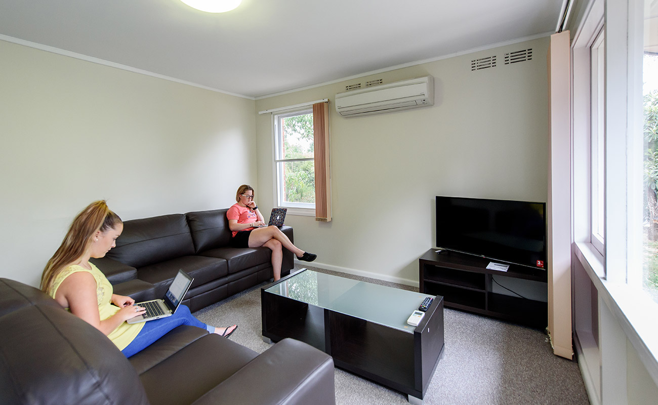A large, clean, white lounge room with brown leather sofas. Two student residents relax, one on their laptop and one reading.