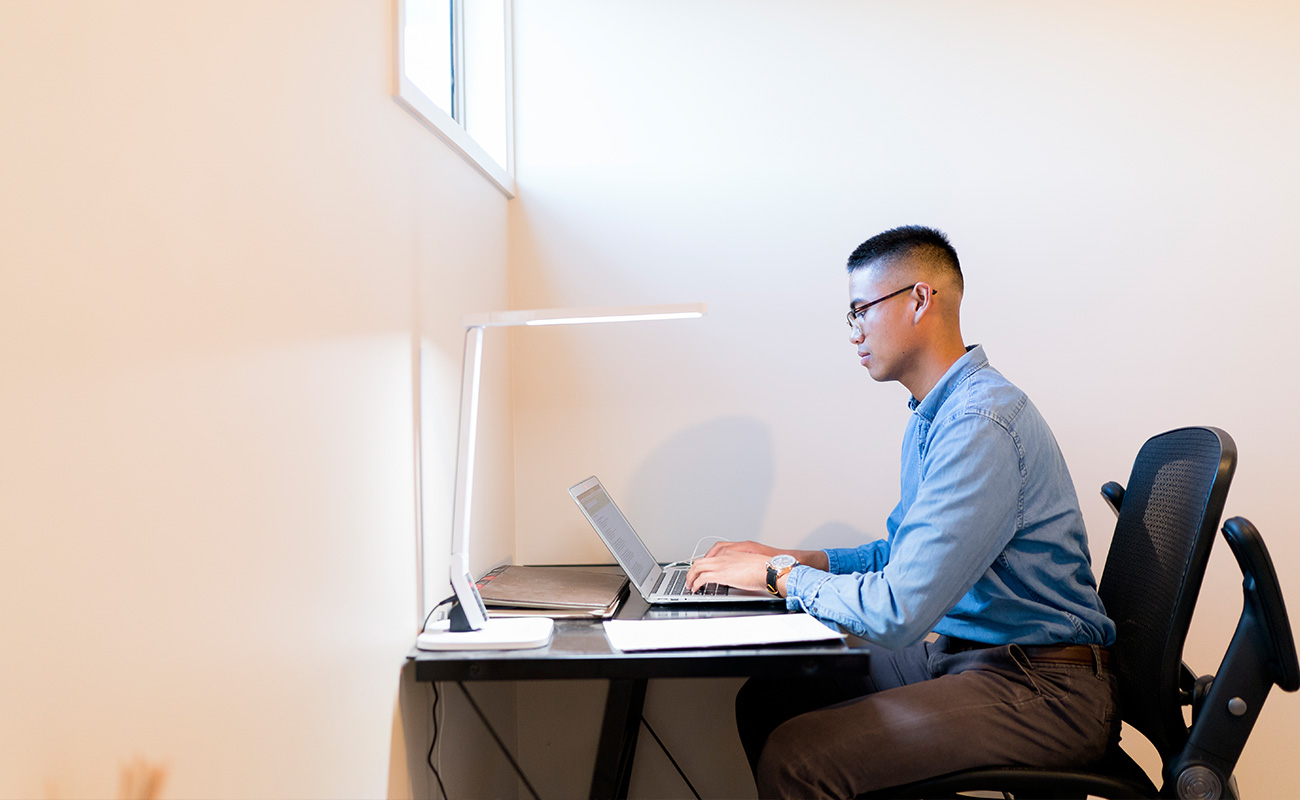 A student resident sits at a desk, on his laptop. Light streams in from a window directly above the desk and from a sleek reading lamp.