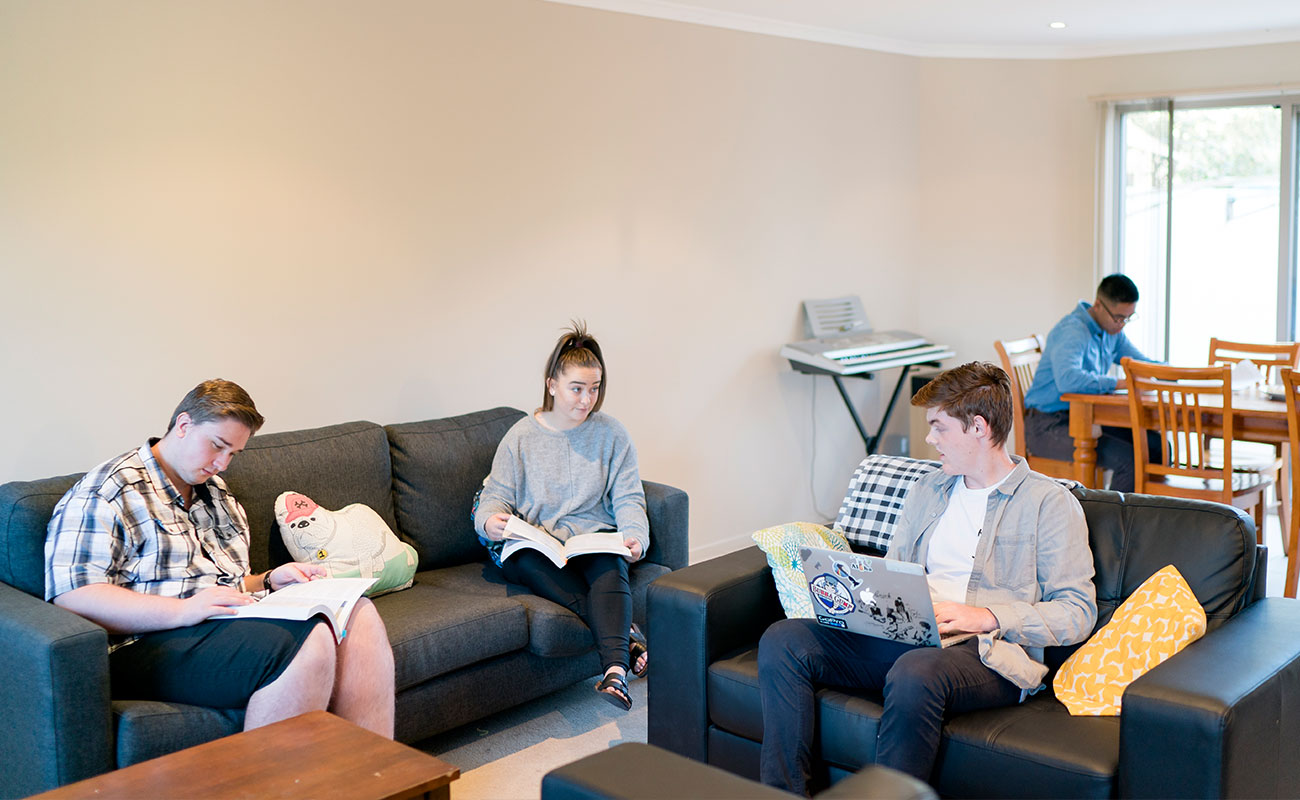 Four students mill about reading in a brightly lit lounge room, with leather couches and wooden tables. One of the students owns an electric keyboard.