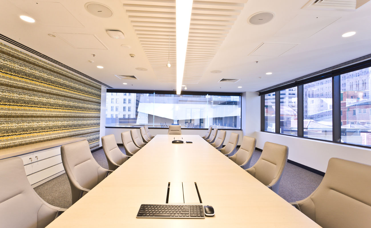 An empty, clean boardroom with white table and chairs.