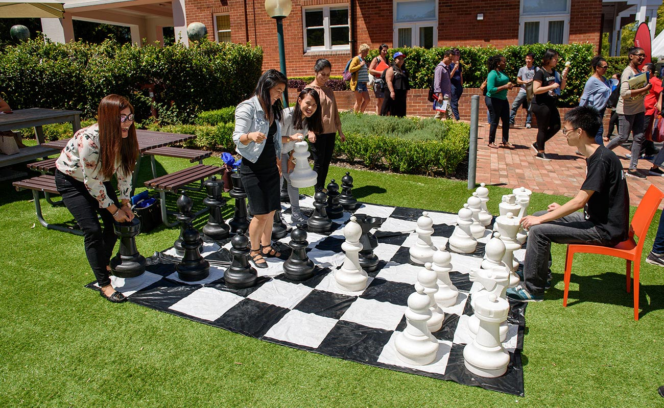 A group of students playing giant chess outside.