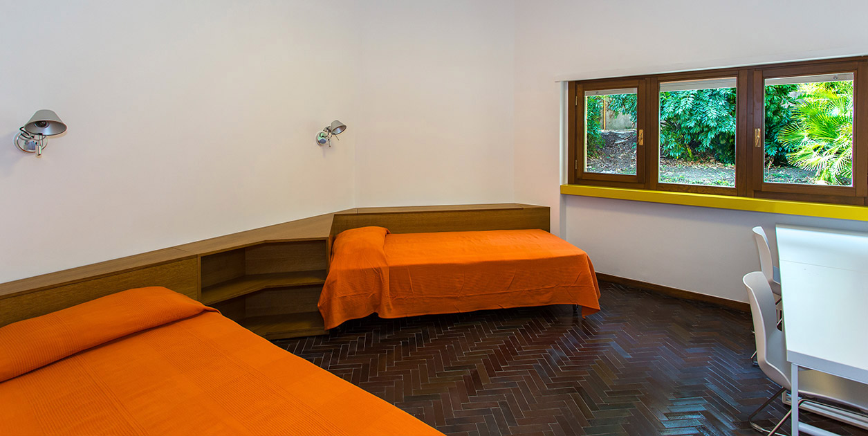 A large open room with orange beds.