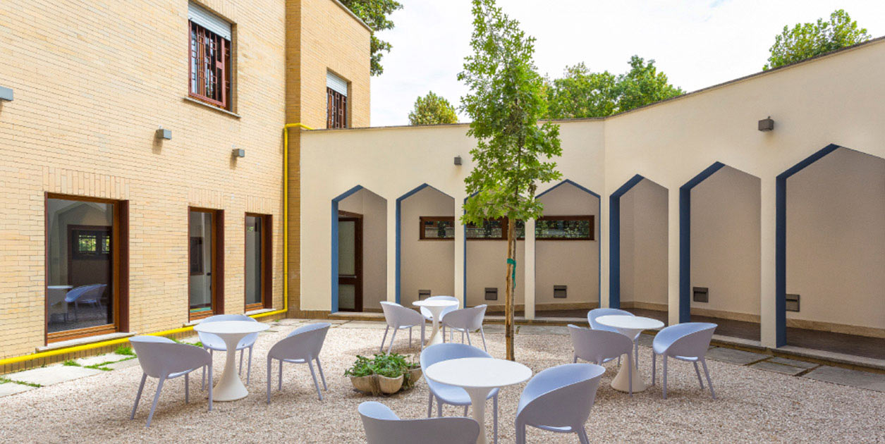 A sunny outside courtyard with small circular tables and chairs.