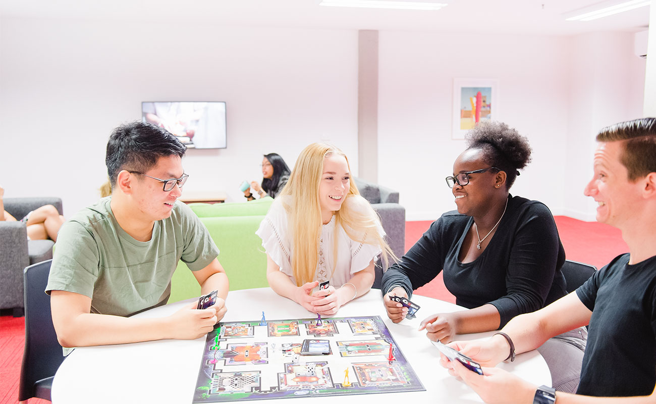 Four students play a board game around a table in a common room.