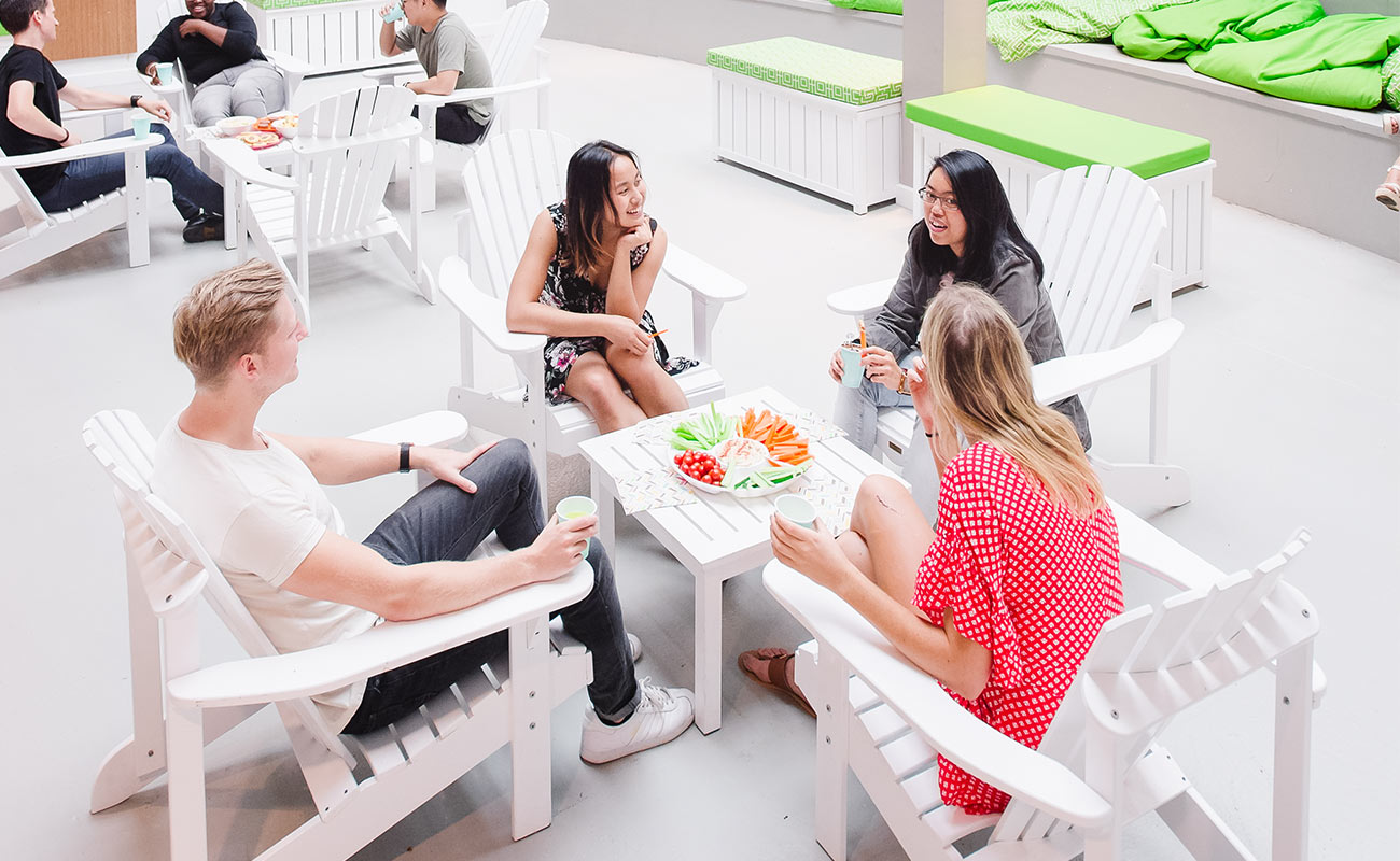 Four students chat on white wooden outdoor furniture with a platter of snacks and drinks.