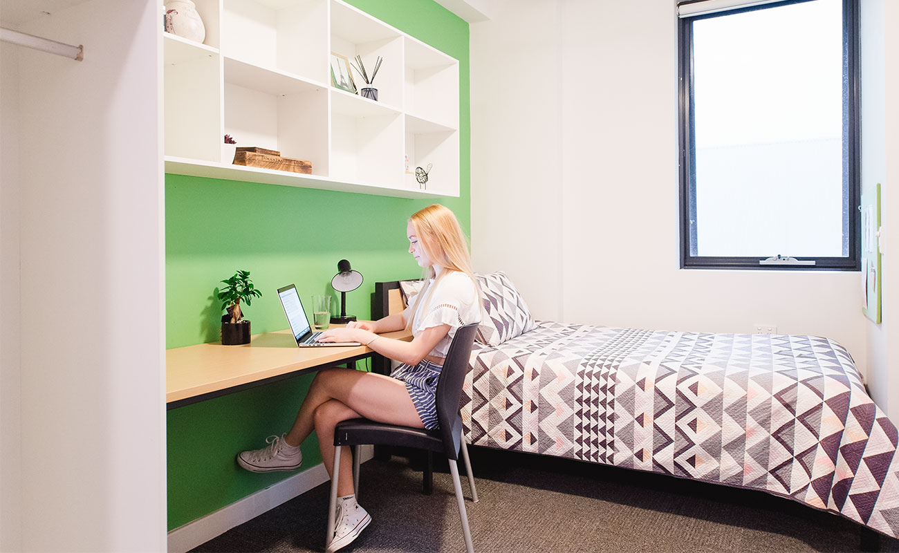 In a studio apartment, a student sits at her desk on her laptop. Above her are shelves and on the wall to her side is her king-single bed.