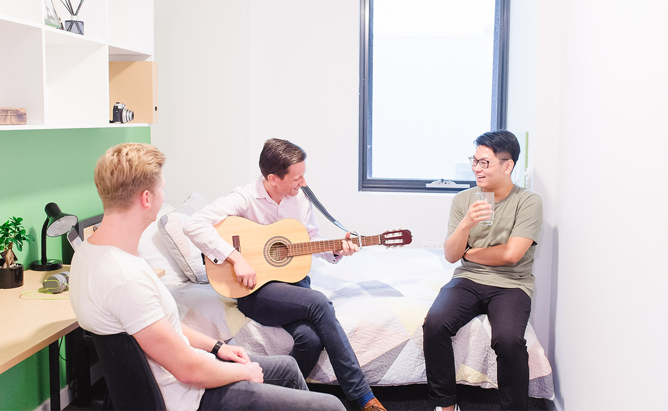 Three students sit in a studio apartment, one is playing a guitar as the others listen.
