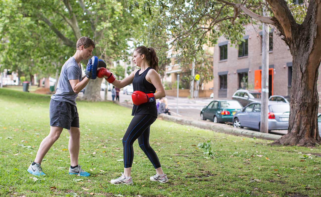 In a park, two students are in exercise wear. One student is punching a bag that another student is holding up for her.