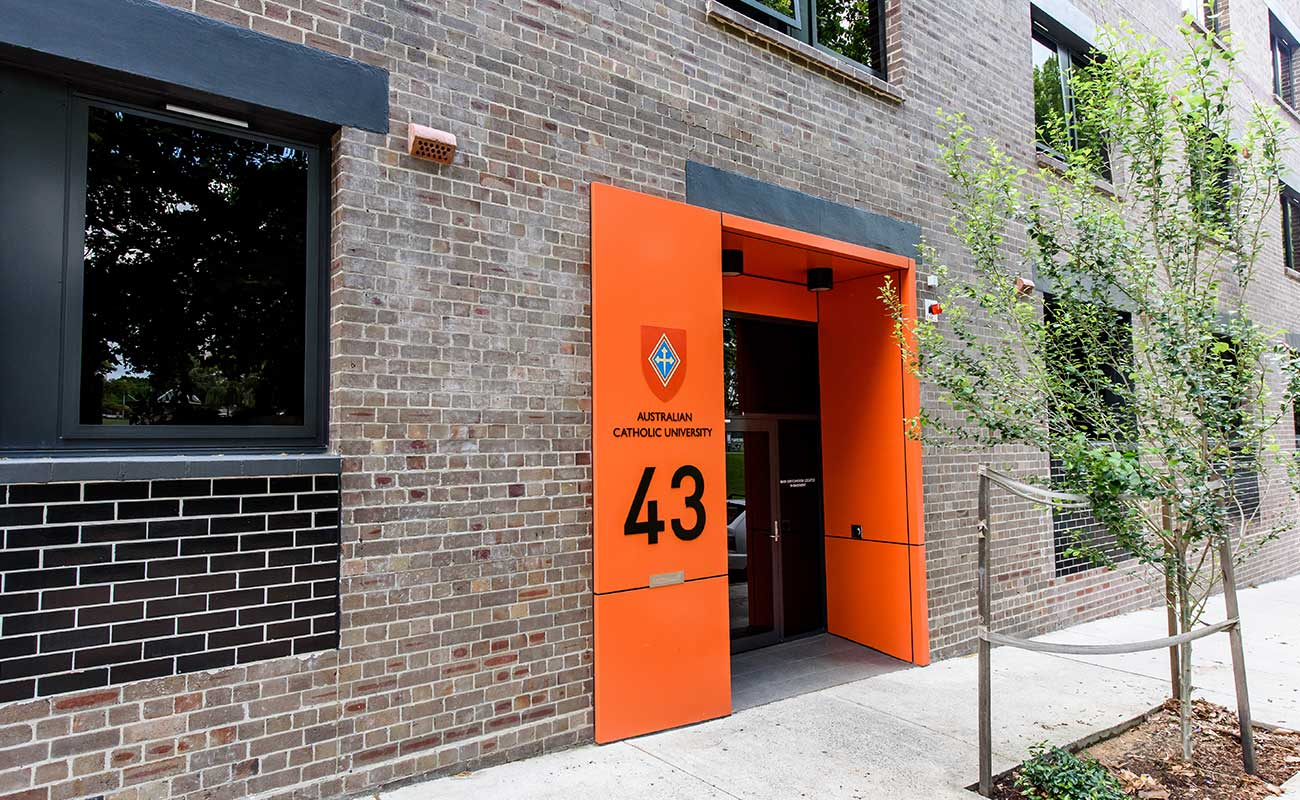 "On a brick building, an bright orange doorway reveals the entrance to the student accommodation it is labelled ""Australian Catholic University 43""."