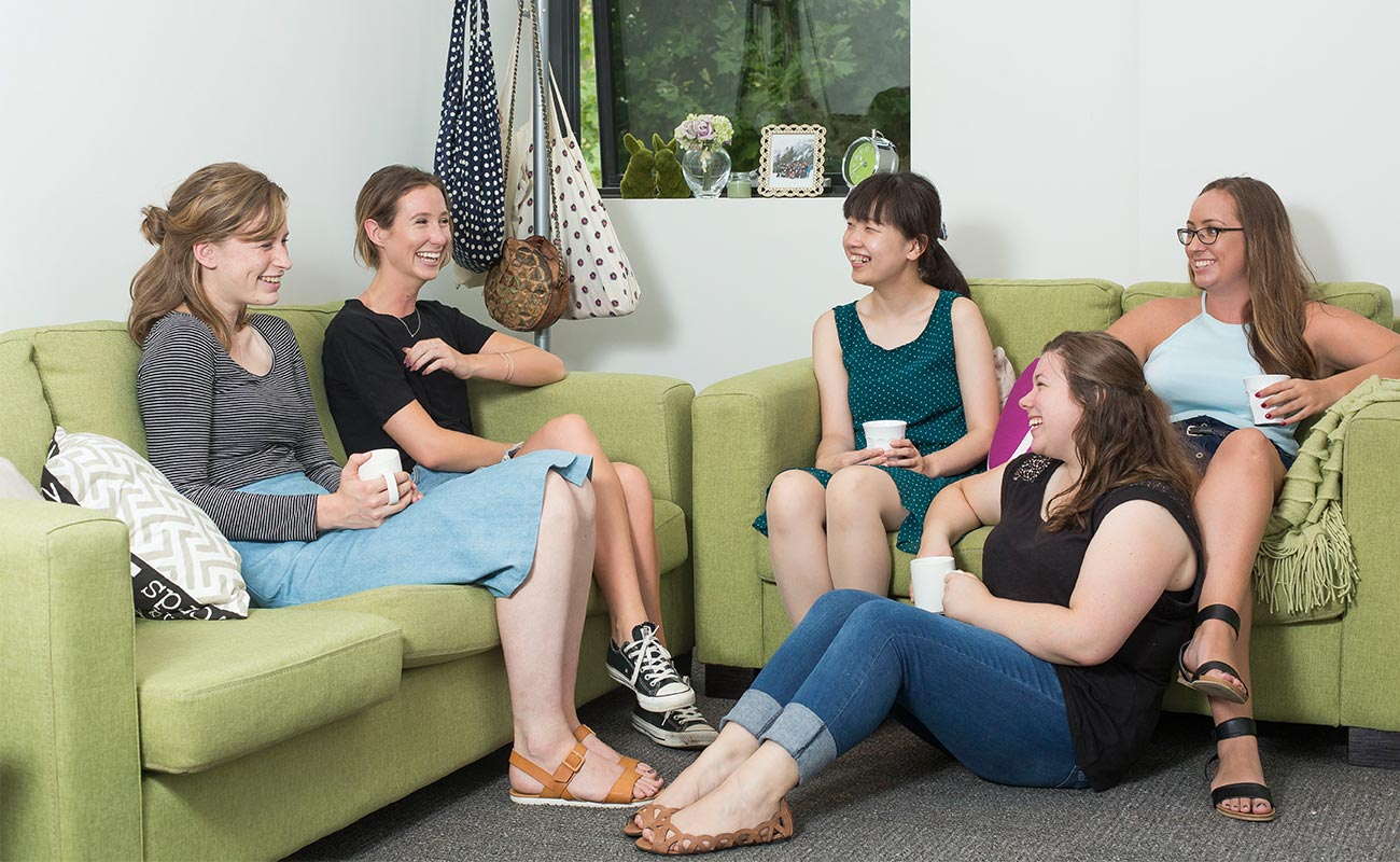 Five female students sit on couches in an apartment, laughing.