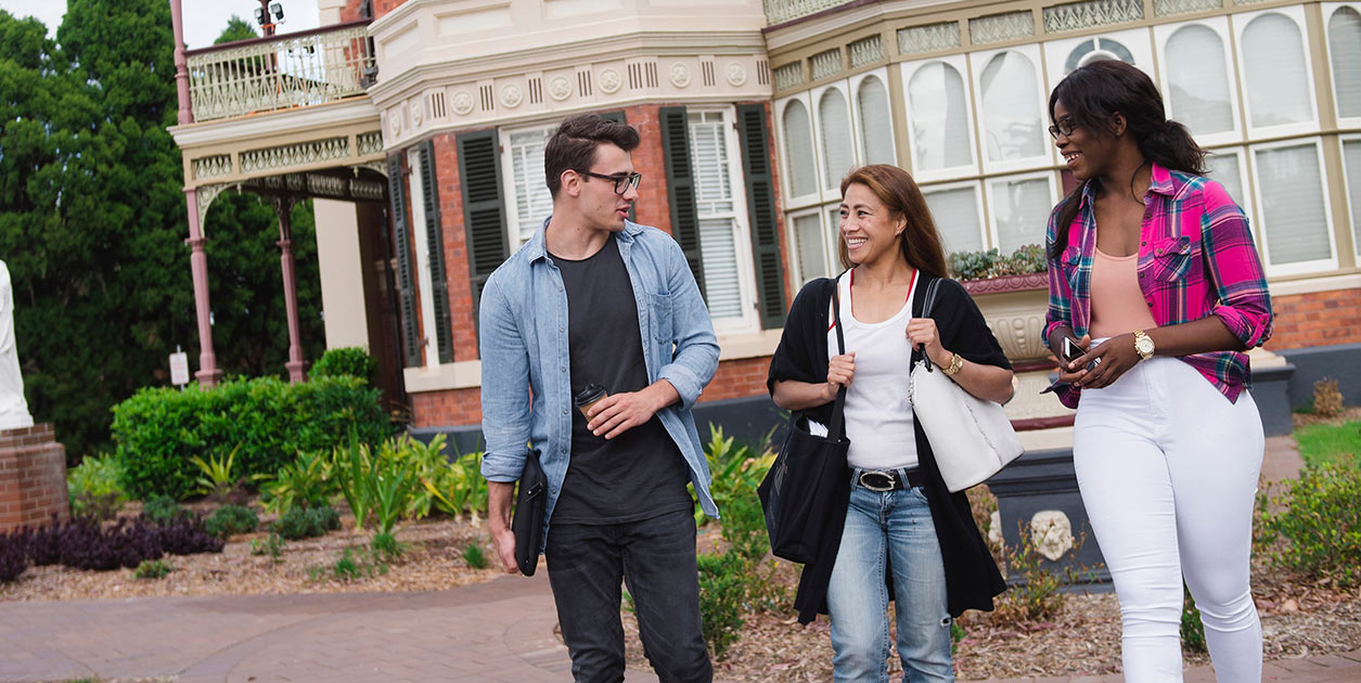 Three students walk side by side outside of the ACU Strathfield campus