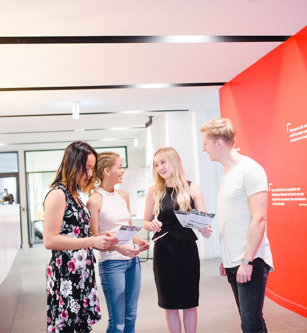 Four students walk through a well-lit hallway, looking at brochures and talking.