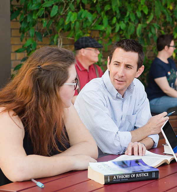 ACU epsitemology and hermeneutics students comparing notes on campus