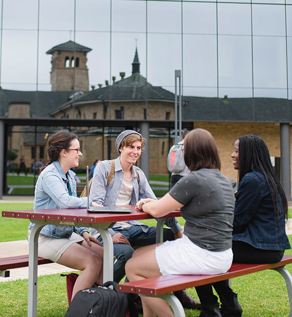 Students sitting around an outdoor table with the reflection of a campus building behind them