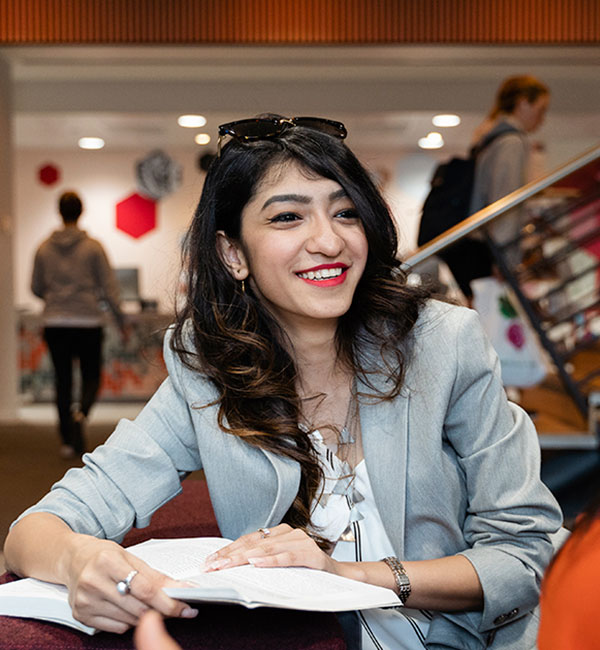 An ACU student smiles warmly while sitting at a desk in the ACU library