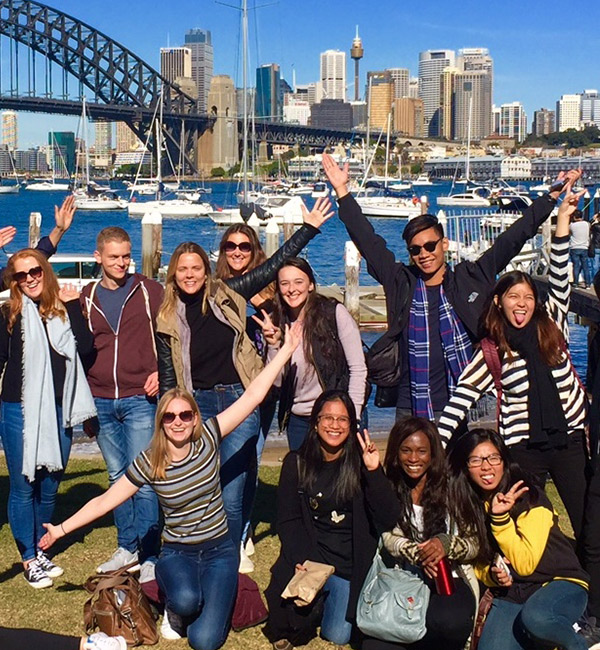 A large group of students poses in front of the Sydney Harbour Bridge