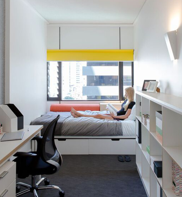 A white studio apartment with desk and shelves, in the background a student reclines in their bed, reading a book.