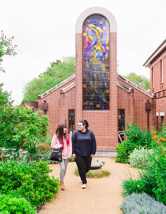 Two students walking and talking amongst gardens, behind them is a brick church a with a large stain-glass window of Mary.