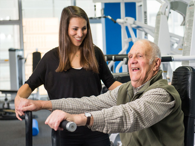 An elderly man is encouraged on an exercise bike by a researcher