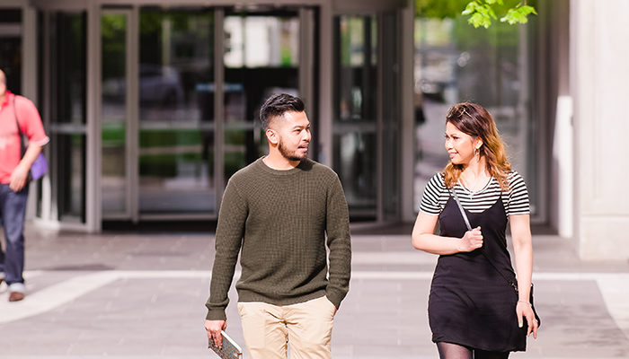 Two students walk through the courtyard of the ACU Melbourne campus
