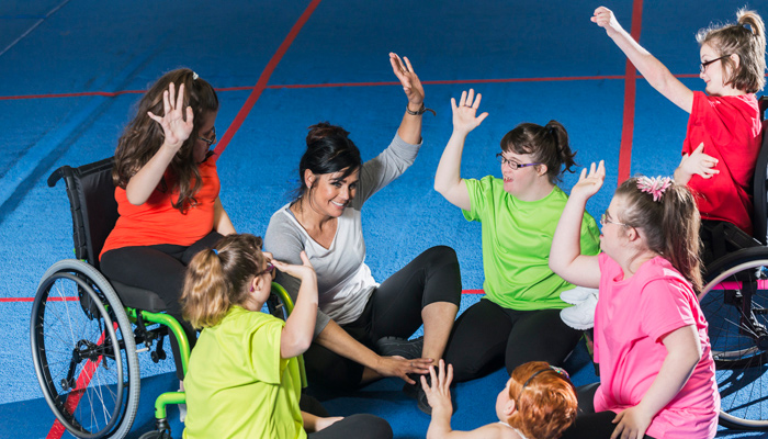 A group of children with cerebral palsy are seated on the floor, in unison they raise their hands alongside a carer.