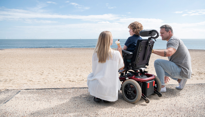 A man and woman couch beside a child in a motorized wheelchair, together they look out on a beach.