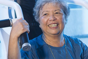 An elderly woman smiles on an exercise machine.