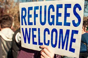 "A hand holding a large sign with words the ""Refugees welcome""."