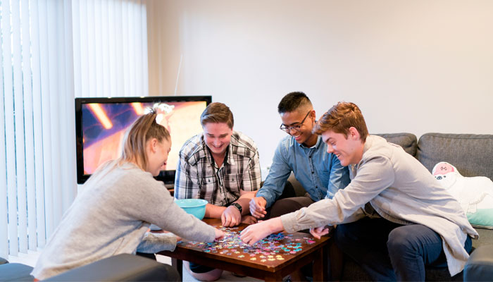 Four jovial students are playing a board game together